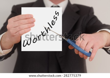 Worthless, man in suit cutting text on paper with scissors - stock photo