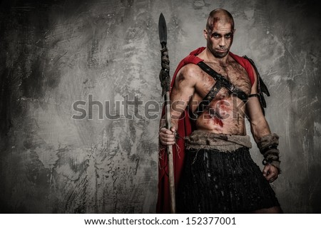 Wounded gladiator in red coat holding spear  - stock photo