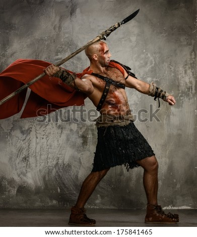 Wounded gladiator in red coat throwing spear - stock photo