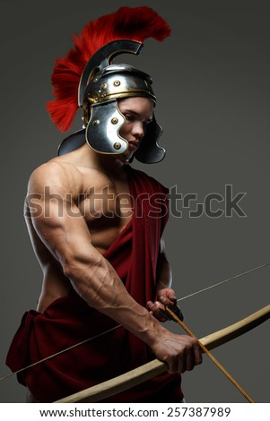 Wounded gladiator with bow isolated on grey.