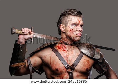 Wounded gladiator with muscular body holding a sword - stock photo