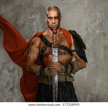 Wounded gladiator with  sword covered in blood isolated on grey