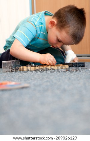 wounded in the left hand with bandage boy at shot in home - stock photo