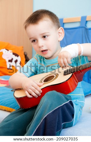 wounded in the left hand with bandage boy at shot in home with guitar - stock photo
