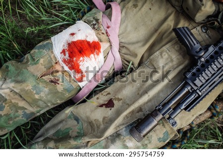 wounded soldiers lying on the grass with arms - stock photo