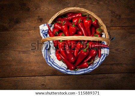 Woven basket full of red chili peppers on wood from above. - stock photo