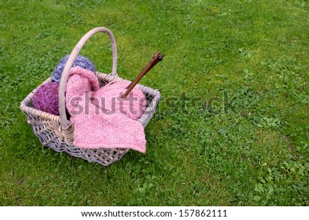 Woven basket of knitting, wooden needles and soft yarn on green grass