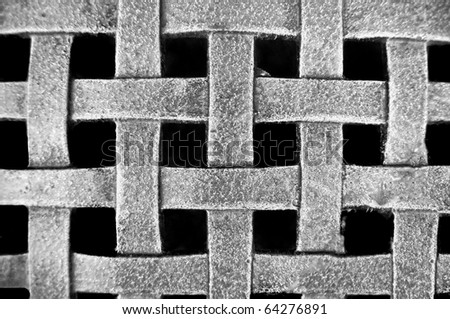 Woven Metal Mesh Grid Pattern on a black background - stock photo
