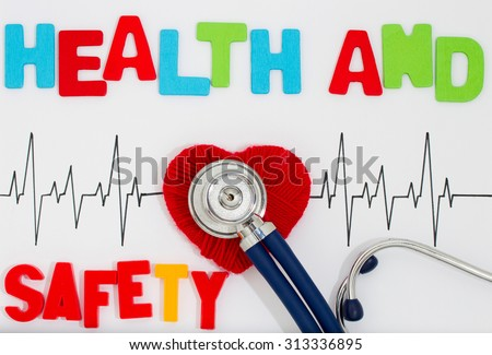 Woven red heart and the stethoscope on the cardiogram. Health and safety - stock photo