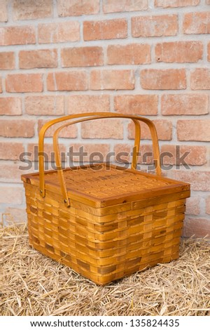 Woven Wood Basket on pile of straw with brick wall background - stock photo