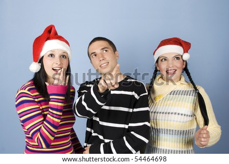 Wow!Look their!The young man pointing somehwere and the girls with Santa hats showing a surprised face and looking up - stock photo
