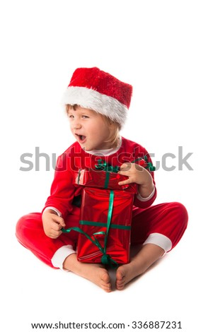 wow Smiling funny child girl in Santa red hat holding Christmas gift in hands. Christmas concept. play with gift - stock photo