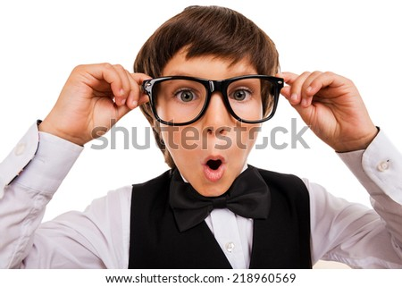 Wow! Surprised little boy keeping mouth open and adjusting his glasses while standing isolated on white - stock photo