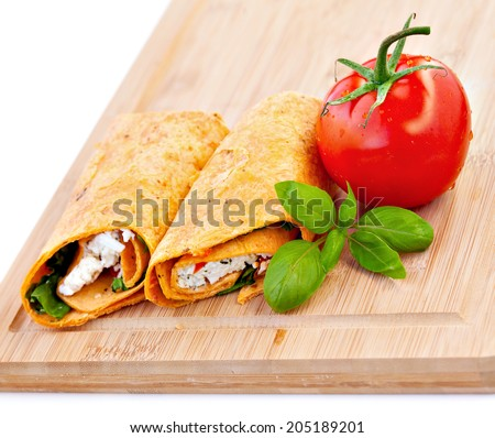 Wrap sandwich with feta cheese tomatoes and basil - stock photo
