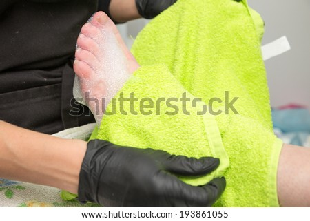 wrap up foot in green towel - stock photo