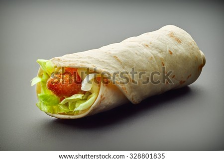 Wrap with fried chicken and vegetables on a gray background - stock photo