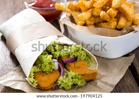 Wrap with fried Chicken (close-up shot) and chips - stock photo