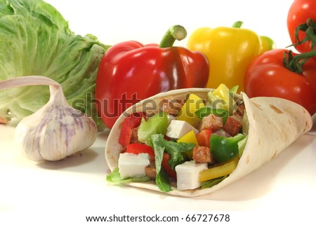 Wrap with mixed vegetables, cheese and turkey strips - stock photo