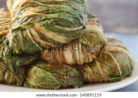 Wrapped and uncut Korean Kimchi on a plate waiting to be cut up. - stock photo