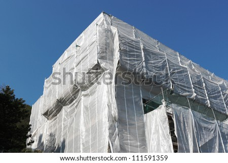 wrapped building at construction site, clear blue sky
