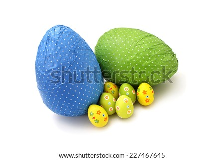 Wrapped chocolate Easter Eggs and little ones on white background - stock photo