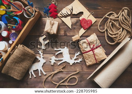 Wrapped Christmas gifts and symbols over wooden background - stock photo