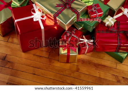Wrapped Christmas presents shot on warm wooden floor includes room for copy - stock photo