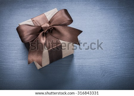 Wrapped gift box on vintage wooden board holiday concept.