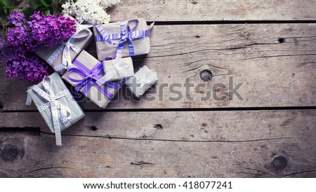 Wrapped  gift boxes with presents  and lila? flowers on aged wooden background. Selective focus. Place for text. Toned image. - stock photo