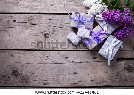 Wrapped  gift boxes with presents  and lilac flowers on aged wooden background. Selective focus. Place for text. - stock photo