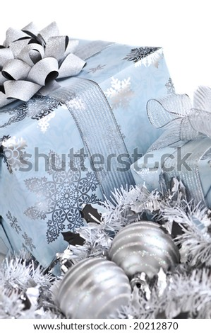 Wrapped gift boxes with silver Christmas ornaments on white background - stock photo