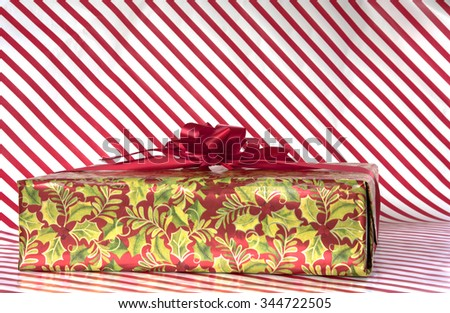 Wrapped gift on red and white striped background for Christmas with copy space