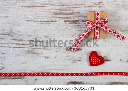 Wrapped gift, Valentine red heart and ribbon on old wooden background, decoration for Valentines Day, symbol of love, copy space for text - stock photo