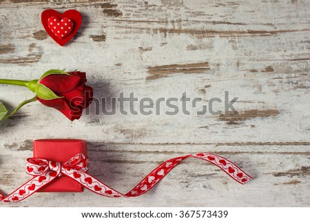 Wrapped gift with ribbon, red heart and rose on old wooden background, decoration for Valentines Day, copy space for text - stock photo