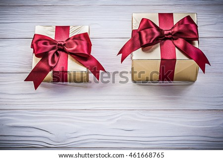 Wrapped giftboxes on wooden board directly above holidays concept.