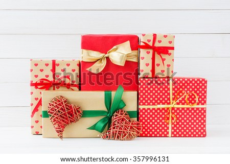 Wrapped gifts boxes and red two red hearts  on white wooden background. Copy space  - stock photo