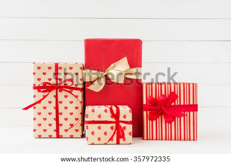Wrapped gifts boxes with red ribbon on white wooden background. Copy space  - stock photo
