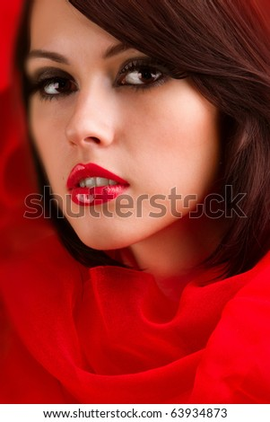 wrapped in scarlet cloth face of a beautiful young girl with a glamorous make-up, where the bright red lips - stock photo