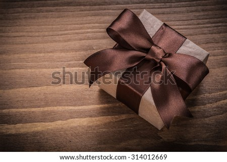 Wrapped present on vintage wood board horizontal version holidays concept.