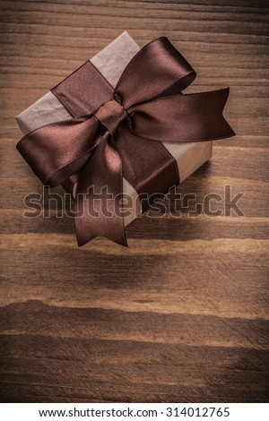 Wrapped present on vintage wood board vertical version holidays concept.