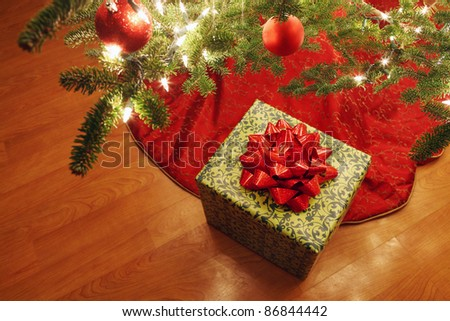 Wrapped present under a Christmas tree - stock photo