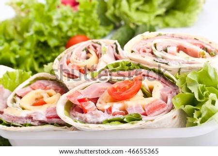 wrapped tortilla sandwich rolls cut in half - stock photo