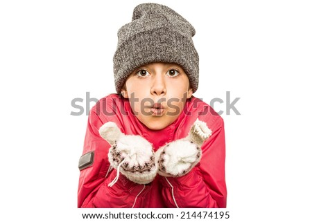 Wrapped up little girl blowing over hands on white background - stock photo