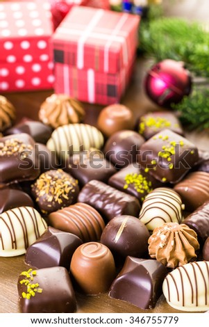 Wrapping assorted chocolates in small boxes for Christmas presents.