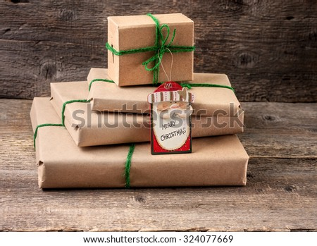 wrapping Christmas presents on an old wooden background in rustic style - stock photo