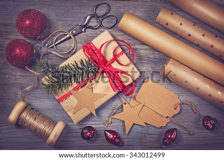 Wrapping paper and a gift on a wooden background - stock photo