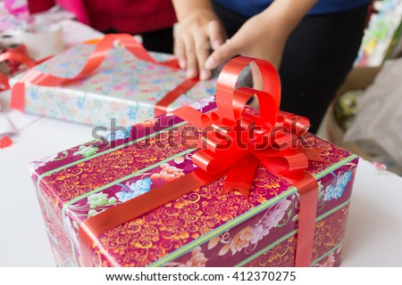 Wrapping presents surrounded by paper, ribbon and bows - stock photo