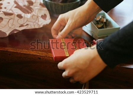 Wrapping red gift with ribbon on wooden table