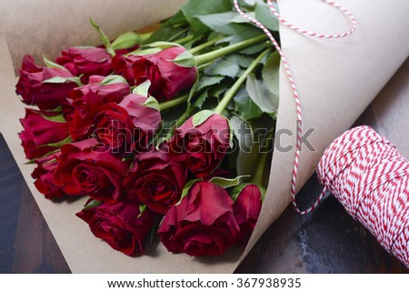 Wrapping Valentine red roses in brown paper on dark wood background. - stock photo