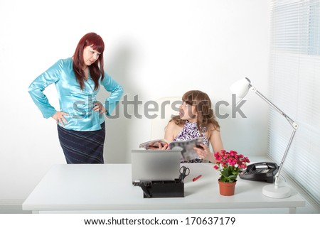 wrathful business woman and a young secretary with magazine - stock photo